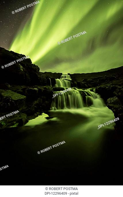 Northern Lights, or Aurora Borealis, glowing over waterfalls and a stream; Iceland