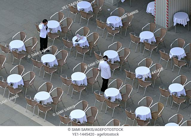 Waiters at empty cafe terrace on Piazza San Marco, elevated view from the Bell Tower, Venice, Italy