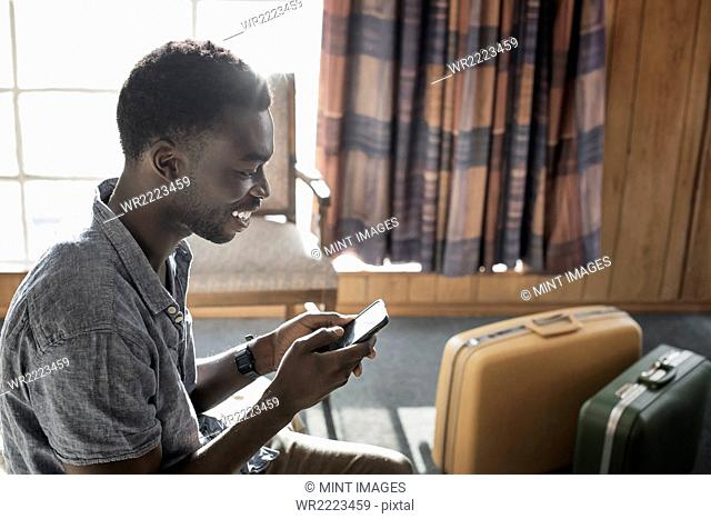 A young man in a motel room checking his smart phone