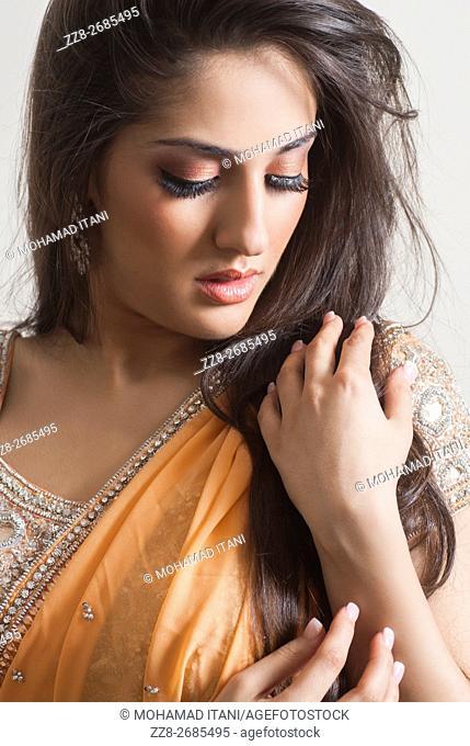 Beautiful Indian woman hands touhcing hair