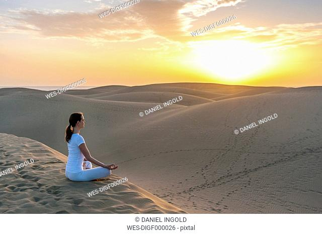 Woman practising yoga on sand dunes