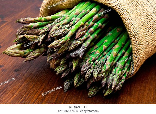 asparagus in burlap sack on wood