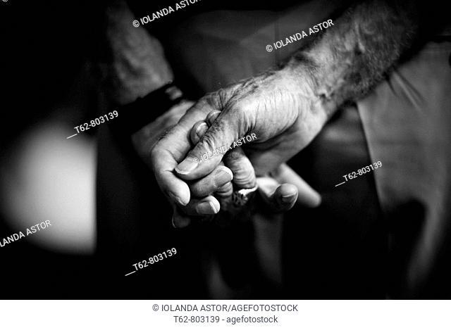 Primer plano manos de hombre, a la espalda; retorciéndose con ansia