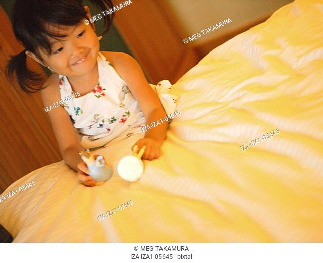 Girl sitting on the bed and holding toys