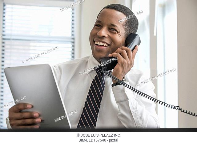 Black businessman on telephone holding digital tablet