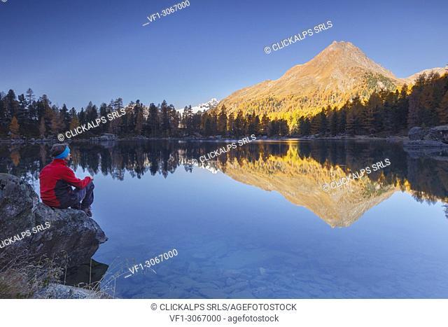 Hiker take a break to admire sunrise on lake Saoseo and Corn da Murasciola mount, Poschiavo, val di Campo, Canton of Graubunden, Switzerland, Europe