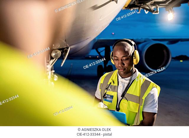 Air traffic control ground crew working under airplane on airport tarmac