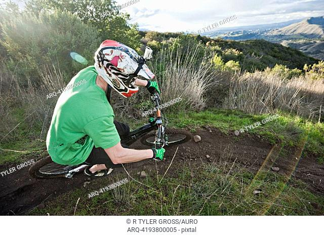 A young man rides his downhill mountain bike on Knapps Castle Trail, surrounded by beautiful scenery in Santa Barbara, CA