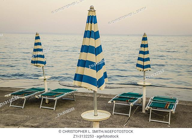 Empty beach chairs with large folded down umbrellas line the waterfront at sundown in Opatija on the Adriatic sea in Croatia