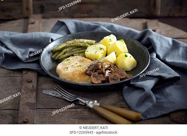Vegan turnip schnitzel with potatoes, green beans and mushrooms