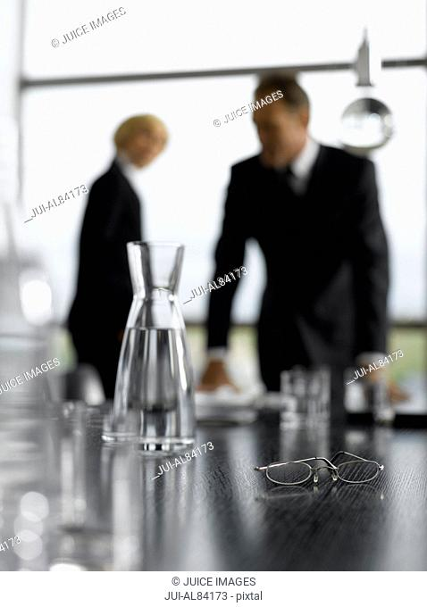 Eyeglasses on table next to water pitcher with businesspeople in background