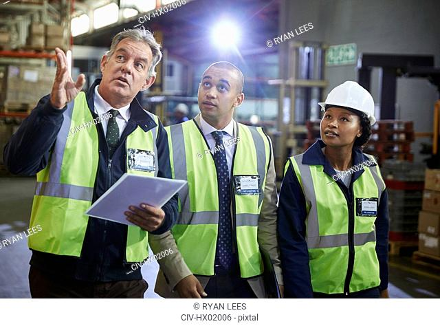 Managers and worker talking looking up in distribution warehouse