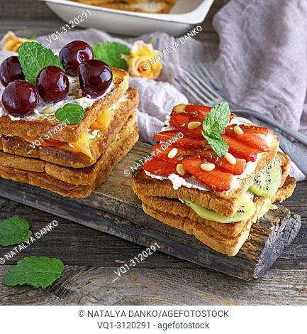French toast with cottage cheese, strawberries, kiwi a wooden board, close up
