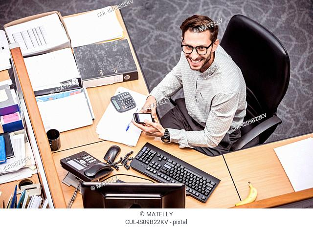 Overhead view of businessman using smartphone at office desk