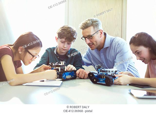 Male teacher helping students assembling robotics in classroom