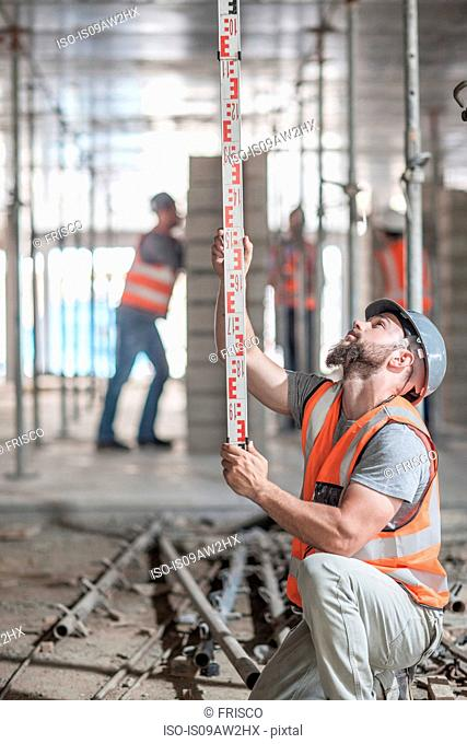 Young male builder measuring construction with ruler