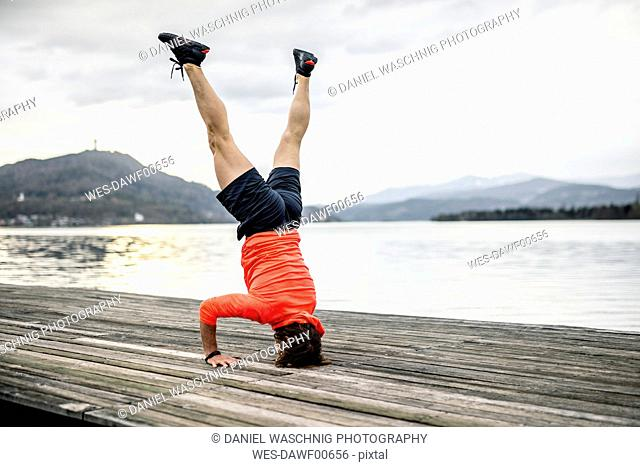 Athlete doing a headstand on wooden deck at the lakeshore