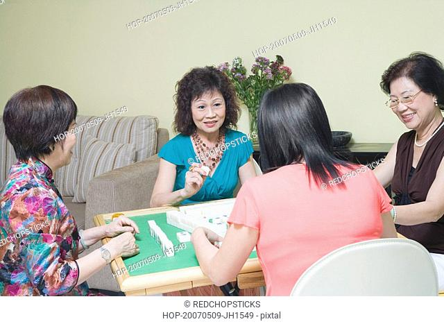 Three senior women and a mature woman playing mahjong