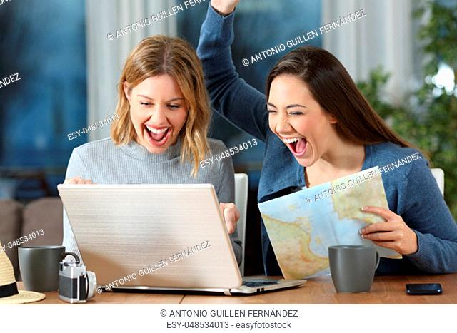 Two excited tourists finding online offer in a laptop at hotel room or apartment