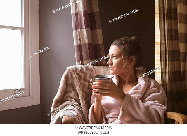 Woman having coffee in bedroom at home