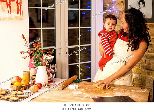Mature woman preparing Christmas cookies with baby son at kitchen counter