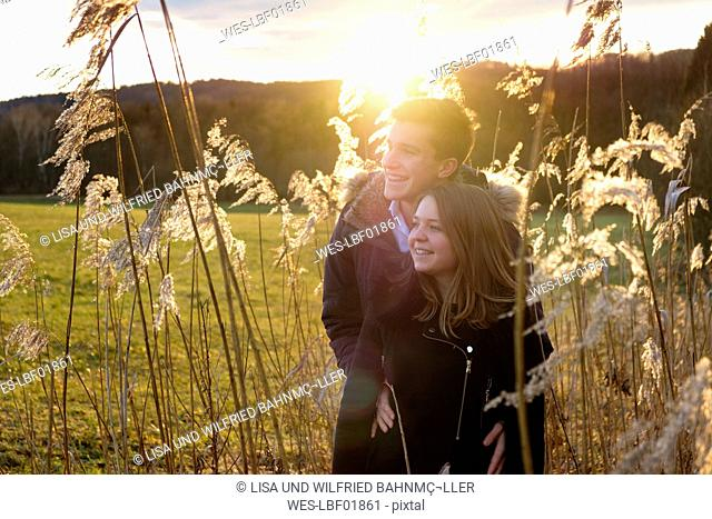 Smiling young couple standing in reed against the sun