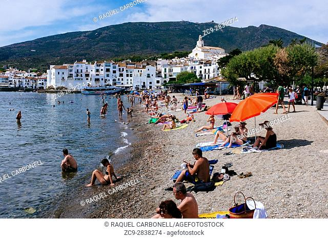 Tourists at the beach with the white village at back. Cadaqués, Alt Amporda, Girona province, Catalonia, Spain