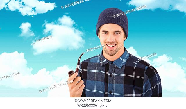 Smiling hipster holding smoking pipe against sky