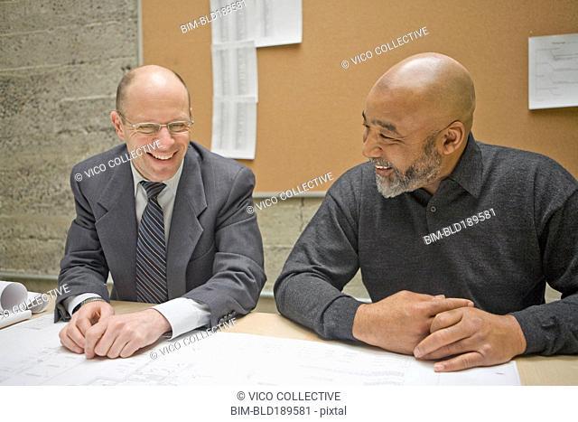 Businessmen reviewing blueprints in meeting