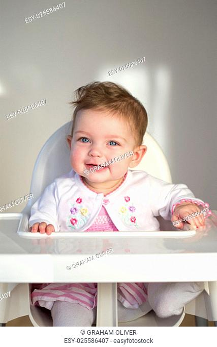 Close up image of a baby girl in her high chair