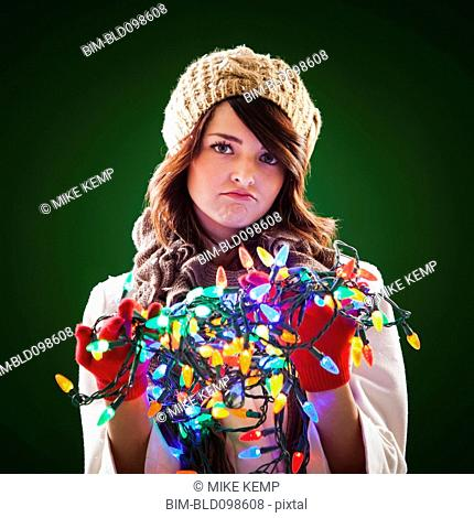 Mixed race woman holding tangle of Christmas lights
