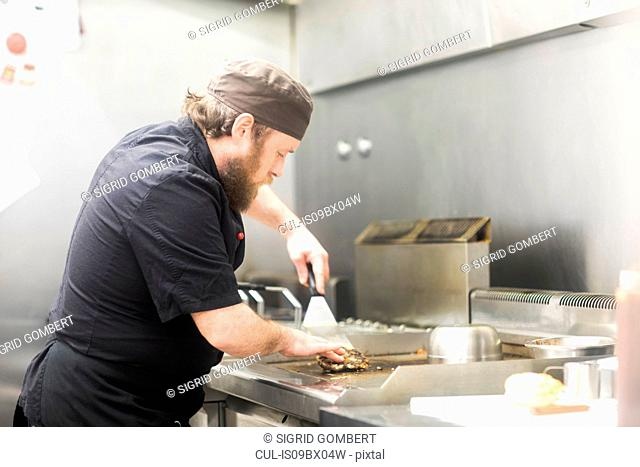 Fast food worker frying burger in commercial kitchen