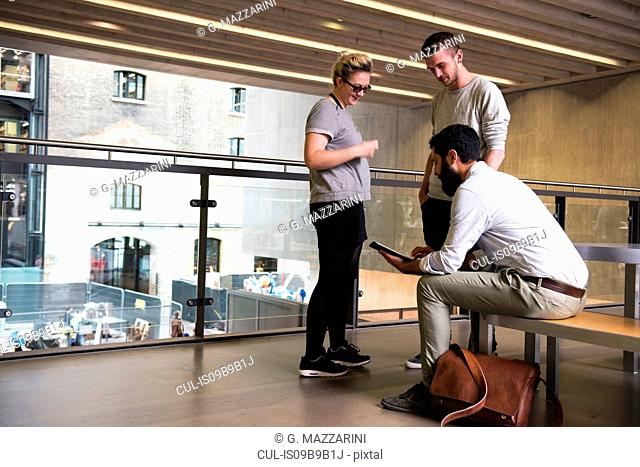 Man with colleagues on mezzanine in office building using digital tablet