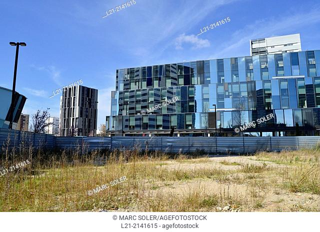 Wasteland, fence, office buildings, blue sky. Plaça Europa, Plaza Europa, District VII, Gran Via, Hospitalet de Llobregat, Barcelona province, Catalonia, Spain