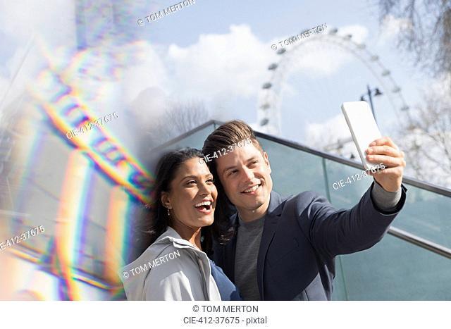 Smiling couple tourists taking selfie near Millennium Wheel, London, UK