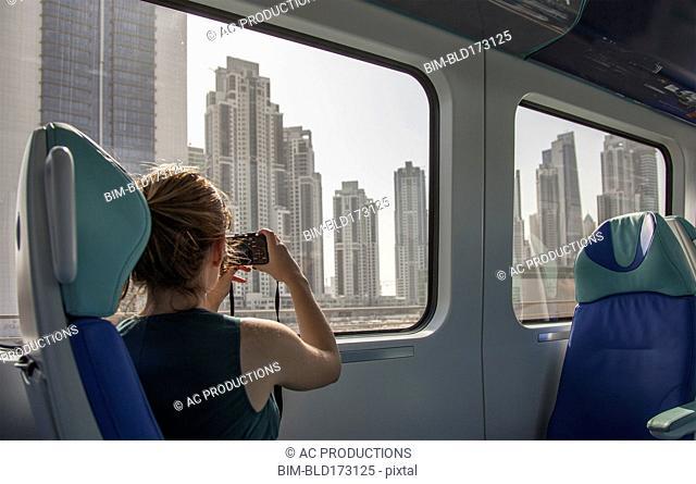 Caucasian woman photographing Dubai cityscape on train, Dubai Emirate, United Arab Emirates
