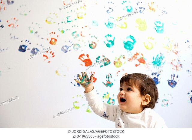 Baby painting a white wall with his hands