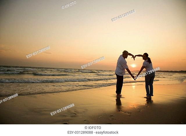 Mid-adult couple making heart shape with arms on beach at sunset