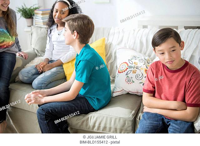 Pouting boy ignoring friends in living room