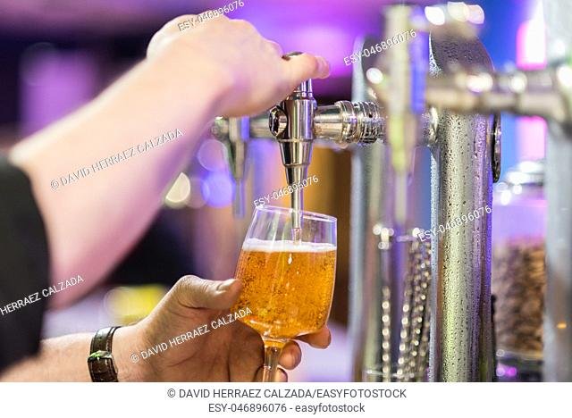 Bartender pouring lager beer in a glass. Shallow dof, selective focus
