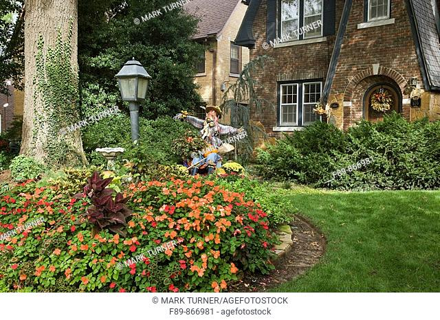 Impatiens in front yard of 1930s brick home with autumn decorations