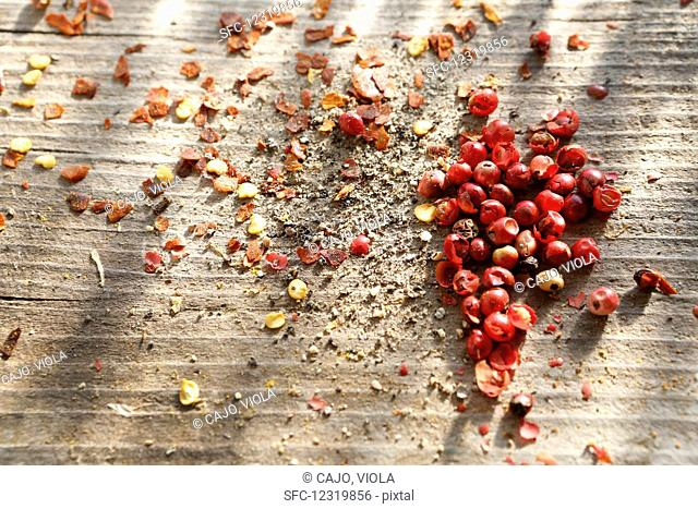 Whole pink peppercorns, ground black pepper and chilli flakes