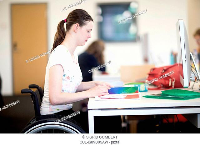 Young female university student using wheelchair reading notes at desk