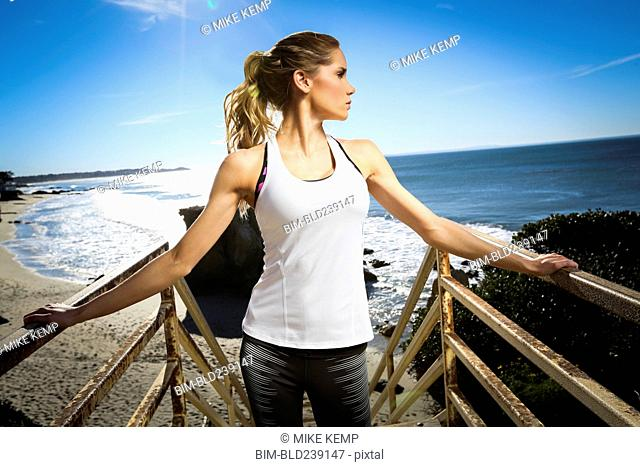 Caucasian woman standing on staircase at beach