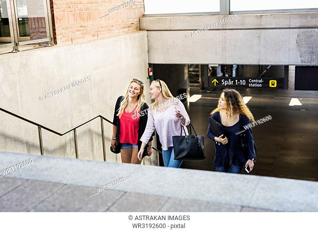 Three young women walking up stairs