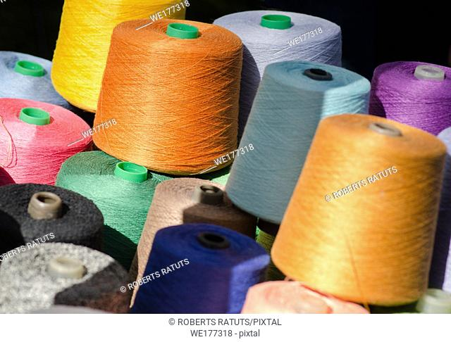 Colorful thread spools, one above the other. Coils with colurful threads