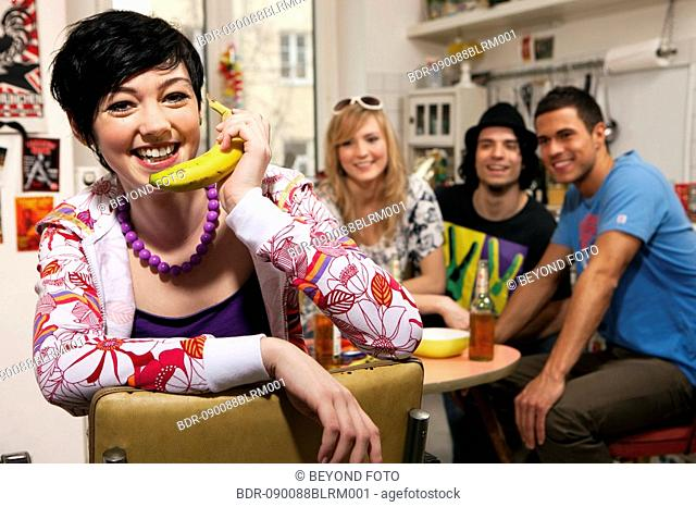 portrait of teenage girl with friends in kitchen using banana as telephone