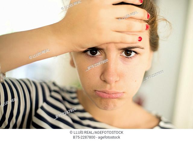 Closeup of a teenage girl with a hand on her forehead and expression fed up and tired