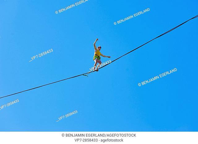 man balancing on highline in Bavarian alps, near mountain Blankenstein, south of Germany