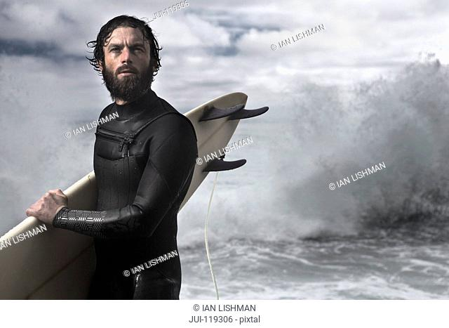 Surfer with surfboard standing on rocks wearing wetsuit with ocean in background and mood sky